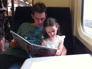 Reading her dinosaur book on the train home